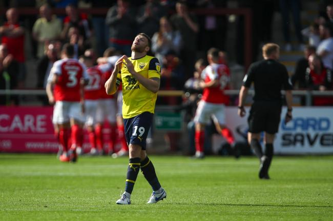 Oxford United skipper Jamie Mackie cannot believe it as Fleetwood's players celebrate scoring what proved the winner on SaturdayPicture: Robbie Jay Barratt