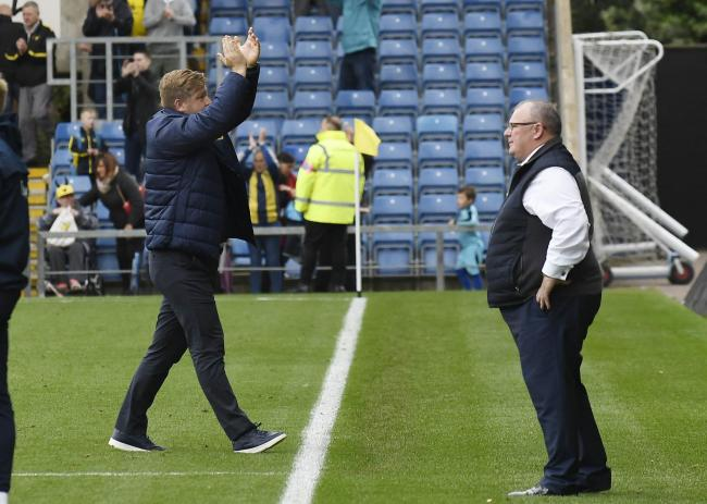 Gillingham boss Steve Evans (right) looks to the pitch as Oxford United head coach applauds the supporters after the victory   Picture: David Fleming