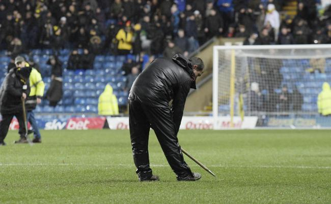 Groundstaff work on the pitch at Oxford United last night  Picture: David Fleming
