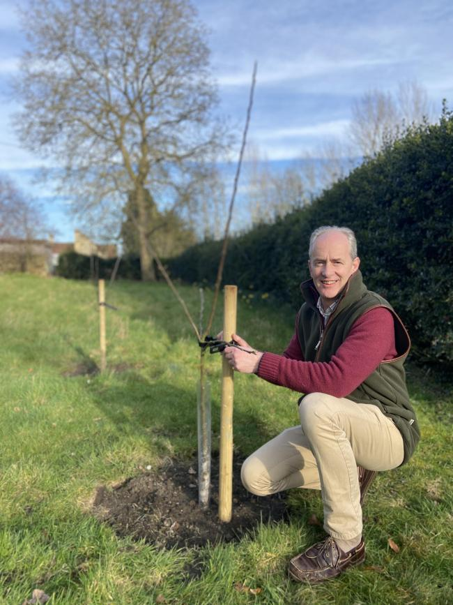 Andrew Myatt posing with one of the first apple trees planted in February