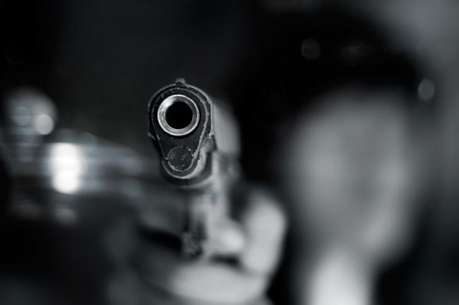 Black and white, woman pointing a old gun to front with one Hand on dark background.