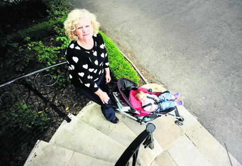 Roz Smith struggles to get a pushchair with her grandaughter Mollie-May Merritt