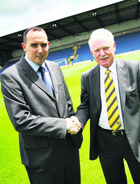 Departing chairman Kelvin Thomas, left, shakes hands with Ian Lenagan at the Kassam Stadium yesterday