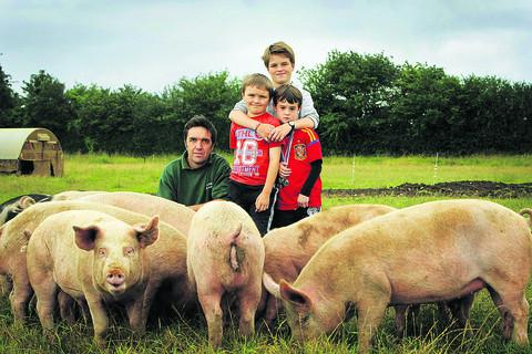 Pig farmer Dave Holloway, of Callow Hill Farm, Stonesfield, with sons Ethan, 11, Freddie, seven, and Ollie, six