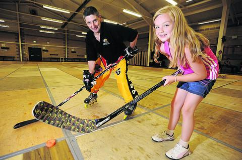 Wilf Iliffe of Banbury Bulldogs Skater Hockey teaches water polo player Holly Showler, seven. She also completed a Sport Relief mile swim