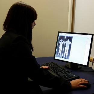 Banbury Cake: A member of staff from Manchester Airport looks at the results of a scan from a 'naked' security scanner