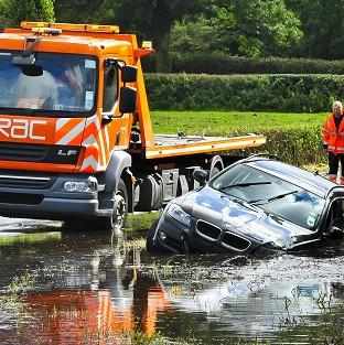 A BMW sits in a ditch surrounded and submerged in flood water in North Somerset after heavy rain has affected roads across the South West