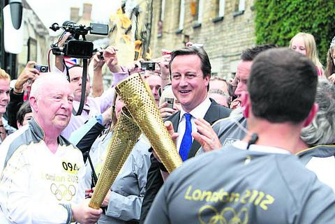 Prime Minister David Cameron watches as Clive Stone passes on the flame in the Market Square in Woodstock earlier this year