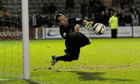 Ryan Clarke pulls off one of his two stops in the penalty shootout that sealed Oxford United's place in the area semi-finals of the Johnstone's Paint Trophy with victory at Plymouth last night