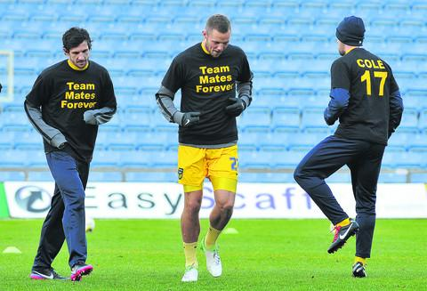 Jake Wright (left) and the Oxford United squad warming up in the commemorative Mitchell Cole T-shirts before Saturday's 1-1 draw with Aldershot
