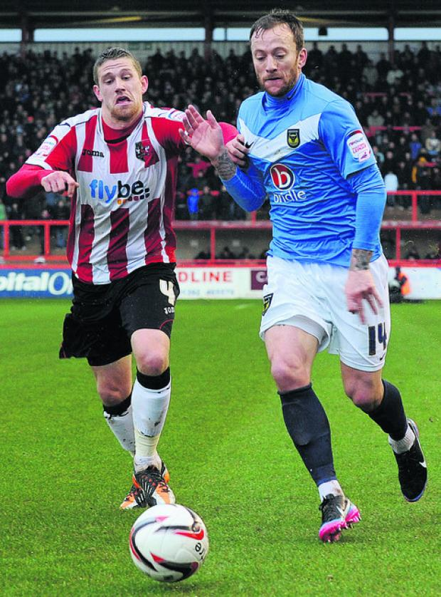 Banbury Cake: Sean Rigg, right, goes past Exeter's Scot Bennett on Wednesday   Picture: Jon Lewis