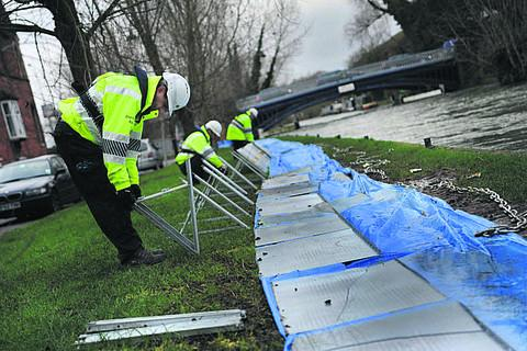Banbury Cake: Environment Agency staff remove the flood defences in West Street and East Street, Osney Island
