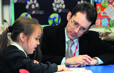 David Lewin, headteacher of Wood Farm Primary School, works with pupil Brianna Bowes