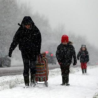A mother and her children make thier way through the snow near Worcester