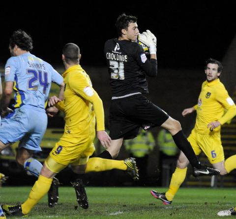 Oxford United keeper Max Crocombe collects a high ball safely