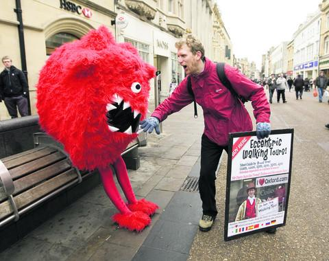 Alasdair de Voil greets the Giant Red Nose Day dinosaur in Cornmarket Street, Oxford