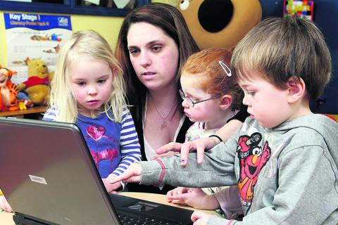 Ella Atkins, four, deputy manager Michelle Bowden, Natalie Anderson, three, and Jake Warner, four, watching nursery rhyme videos on the laptop donated to the Oxford Nursery