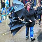 Banbury Cake: Shoppers struggle with their brollies at Carfax as high winds and heavy rain swept the county yesterday