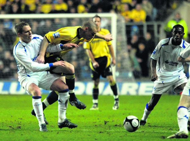 Nicky Wroe gets to grips with James Constable when Torquay United played at the Kassam Stadium in 2009