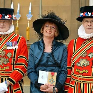 Artist Grayson Perry holds his CBE presented to him by the Prince of Wales during an investiture ceremony at Buc