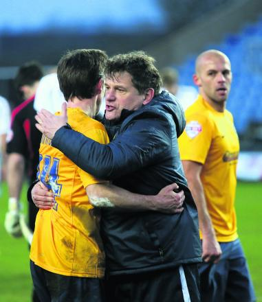 Mickey Lewis gives David Connolly a well-deserved hug after his debut goal helped Oxford