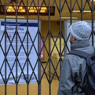 A man looks through locked gates at London Bridge station during the strike