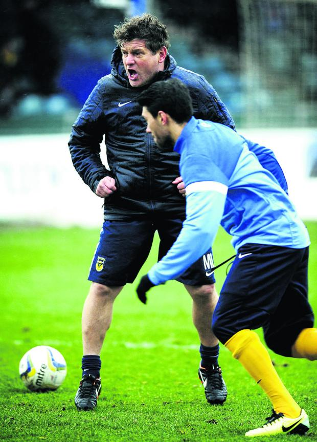 Banbury Cake: Mickey Lewis shouts the orders as he takes the pre-match warm-up at Bristol Rovers last week