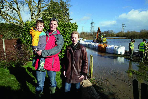 Nicola Blackwood MP views progress on South Hinksey's flood barrier in the garden of Adrian Porter pictured with his son, Torin, two