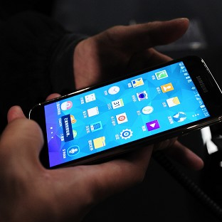 The new Samsung Galaxy S5 is examined by a visitor to the Mobile World Congress, the world's largest mobile phone trade show in Barcelona (AP)