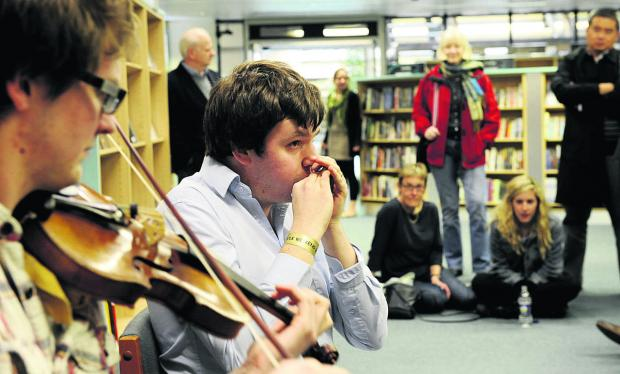 Will Pound plays the harmonica at Westgate Library alongside fiddle player Henry Webster Picture: OX51557 David Fleming