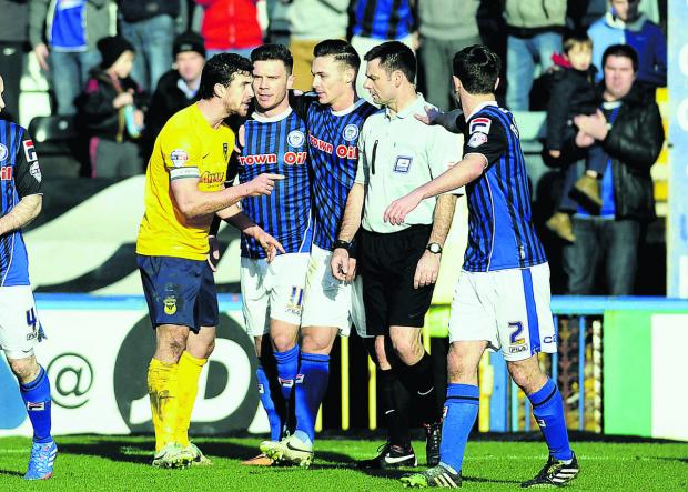 Jake Wright argues with referee Eddie Ilderton after Scott Hogan, who looked su