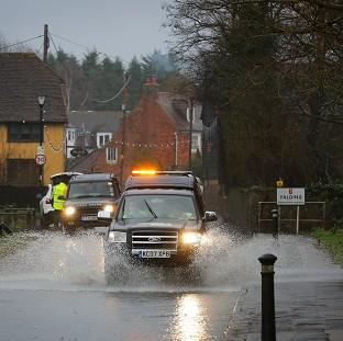 Banbury Cake: A car passes through a flooded road in Yalding, Kent