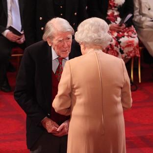 Raymond Roberts receives his Member of the British Empire medal from the Queen durin