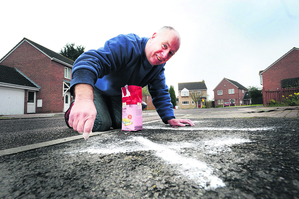 Iain Belton draws some hash run markings outside his home in Bicester