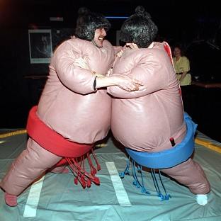 A man knocked himself out when he bounced off a work colleague while wearing an inflatable sumo suit