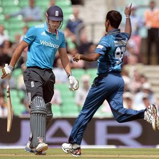 Nuwan Kulasekera, right, celebrates taking the wicket of England captain Alastair Cook