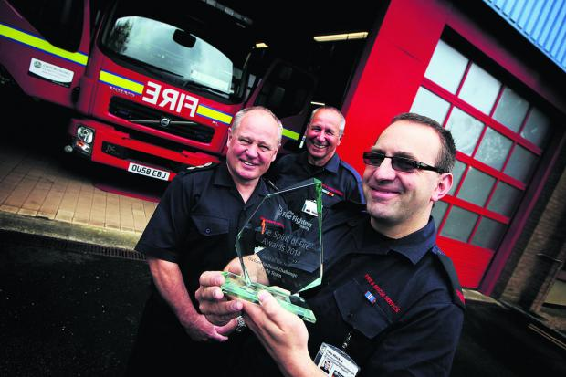 Firefighter Pete MacKay holds the award with station manager Simon Sumners, left, and resources manager Clive Durbin Picture: OX67475 Ed Nix