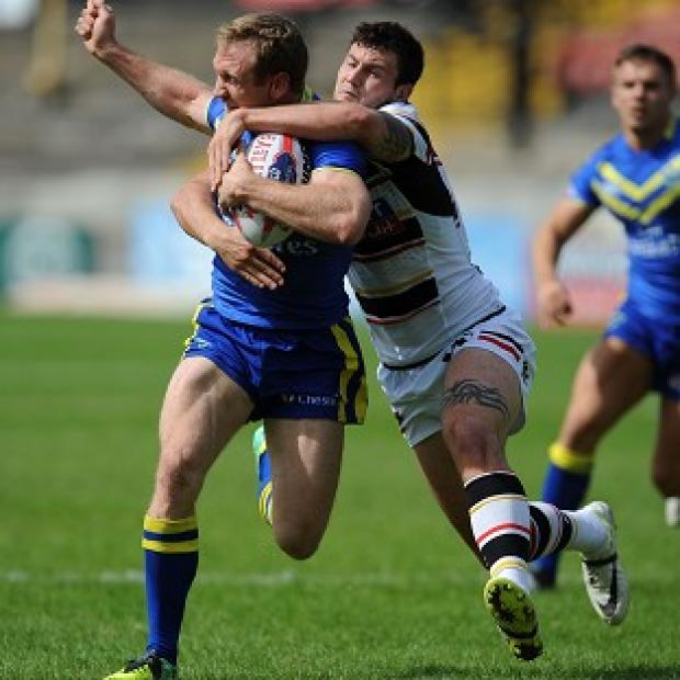 Banbury Cake: Michael Monaghan, pictured being tackled by Bradford's Jay Pitts, suffered an injury in Warrington's semi-final win
