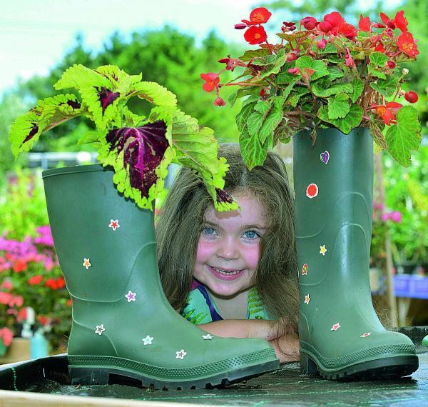 Matilda Hillis, four, with wellies filled with flowers during a free children's welly-planting activity at Bicester Avenue Garden Centre in Bicester. Picture: OX68807 Simon Williams