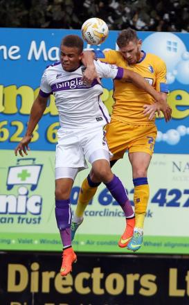 Oxford United's Carlton Morris (left), seen battling it out with Mansfield Town's Ritchie Sutton in the 2-1 defeat on Saturday, feels the U's are set to turn the corner