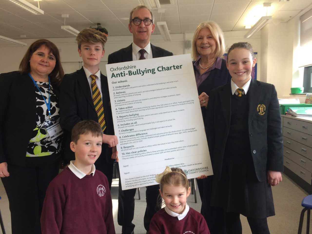 Oxfordshire County Council's cabinet member for education and public health Hilary Hibbert-Biles (second right) presents the anti-bullying charter to Chipping Norton School headteacher Simon Duffy (back, centre) and St Mary's Primary School headteache