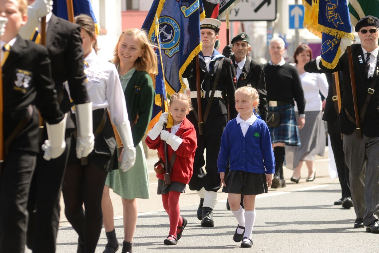Tiny standard bearer carries flag at remembrance service for new generation