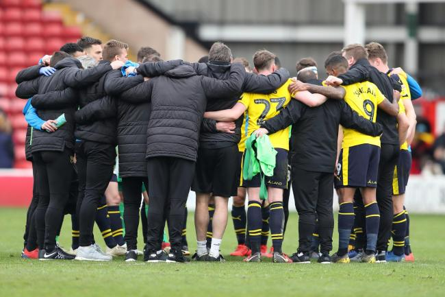 Oxford United players in a huddle at full time after their win at Walsall last season
